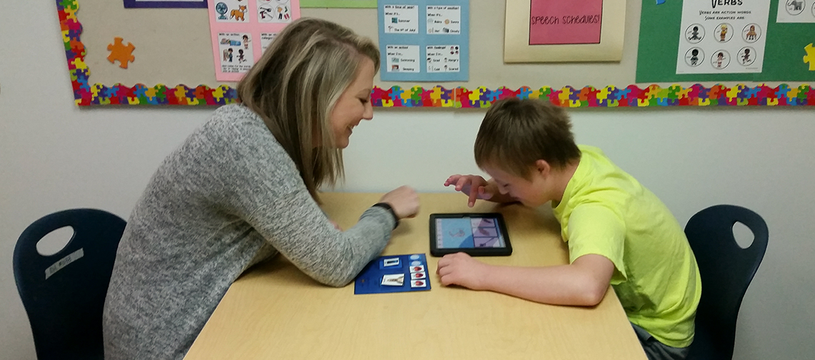 Speech Pathologist using assistive technology to teach a Monarch student with Autism Spectrum Disorder